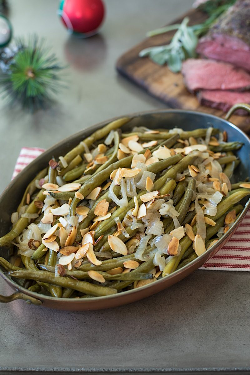 Green beans in an oval copper serving dish with beef tenderloin in the background