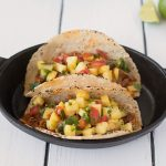 Carnitas tacos topped with pineapple salsa
