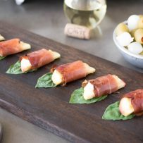 Apple slices wrapped in prosciutto with basil on a wooden board