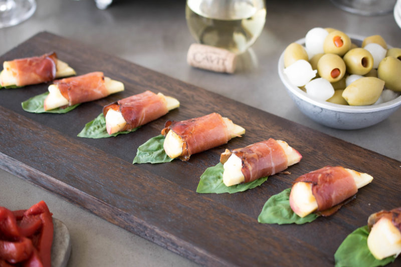 Smoked prosciutto wrapped apple bites lined up on a serving board