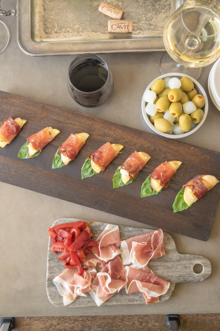 The bites served on a board with sliced meats, olives and wine