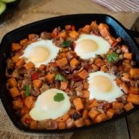 Sweet potatoes, sausage and bacon cooked in a cast iron skillet topped with 4 sunny side up eggs