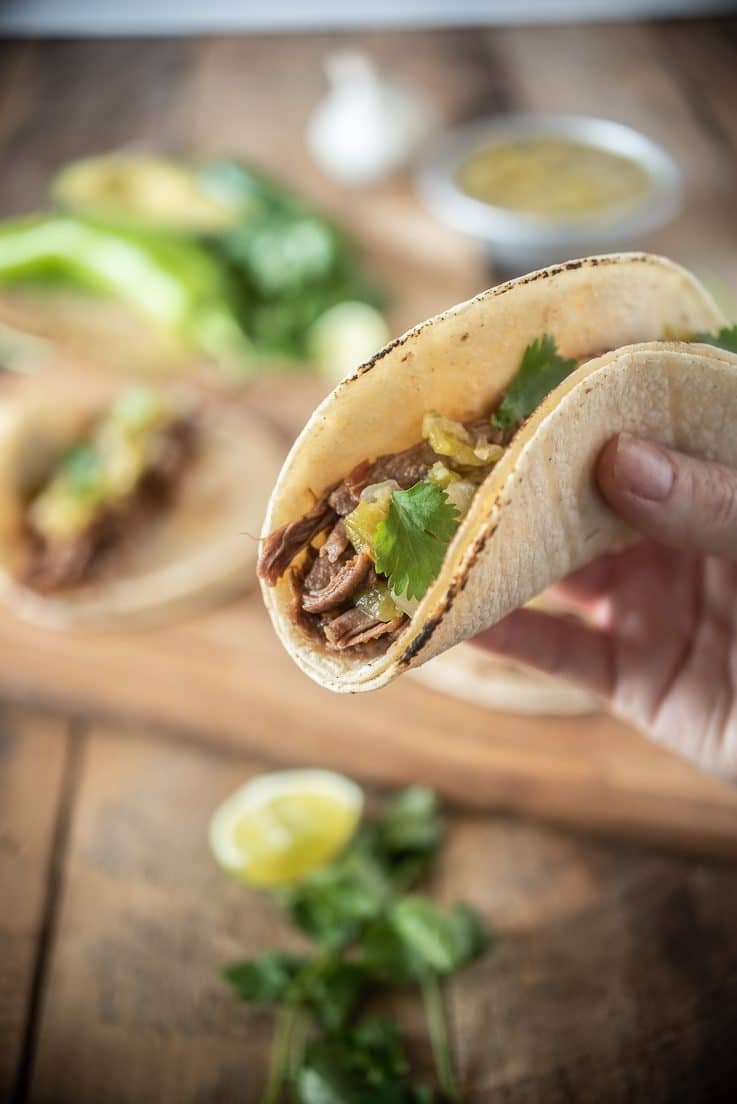 A closeup holding a taco with garnishes in background