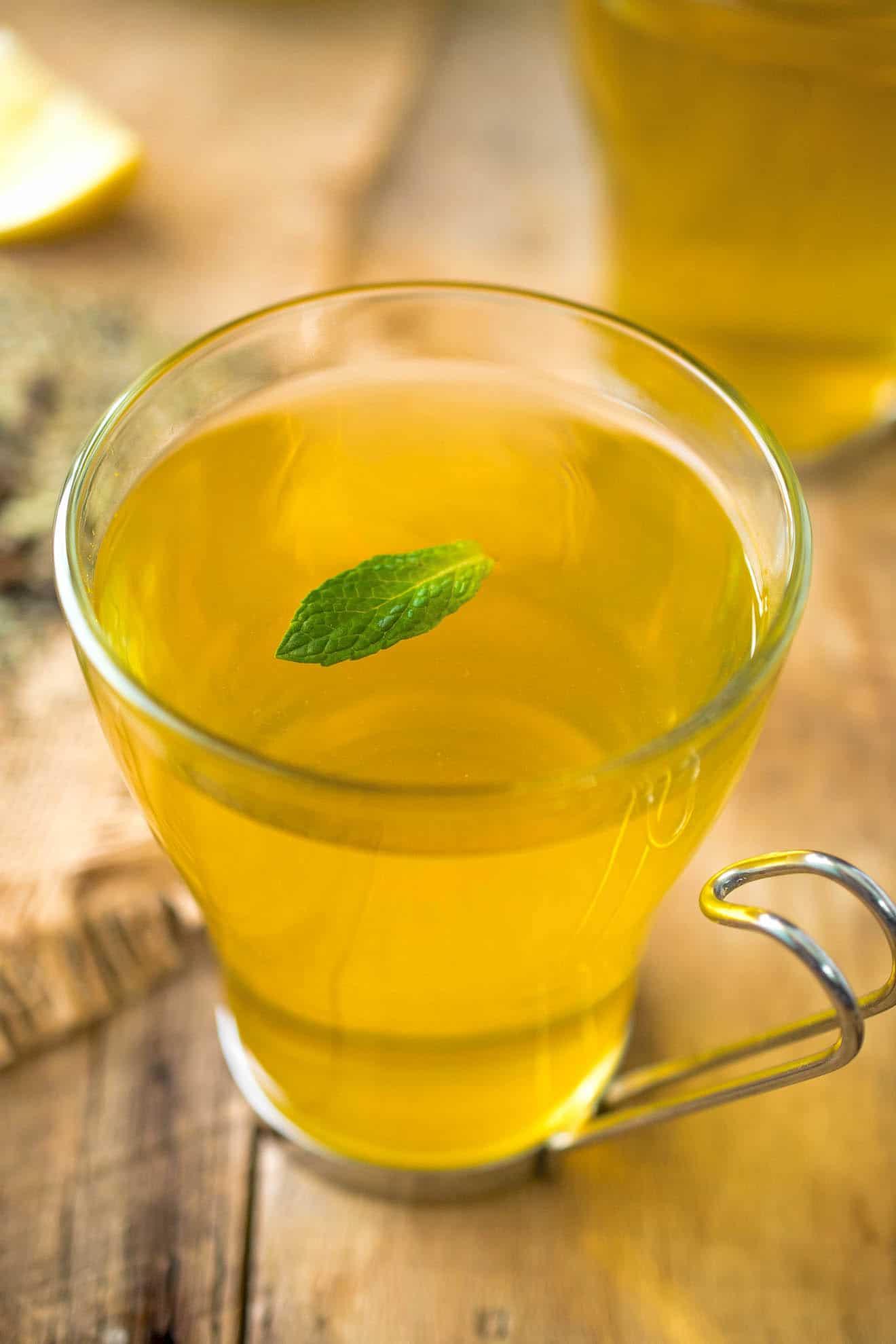 A glass mug of herbal tea with a mint leaf garnish