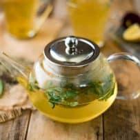 Fresh herbs floating in herbal tea in a clear teapot