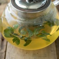 A closeup of soothing therapeutic herbal tea in a glass teapot with fresh herbs