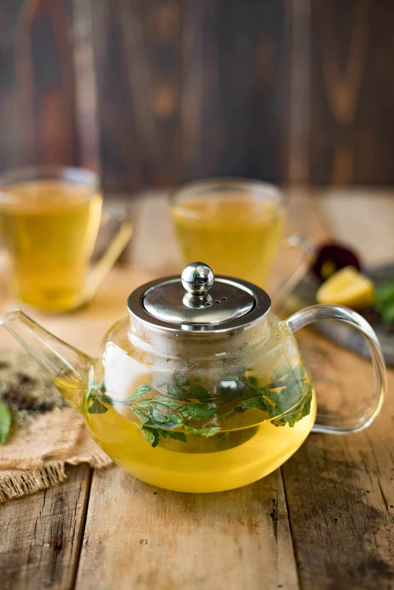 Fresh mint in a glass teapot of herbal tea with cups