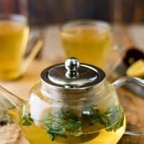 A glass teapot of herbal tea with fresh herbs
