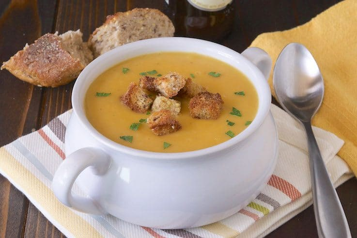 Soup served in a white crock bowl with a spoon and croutons