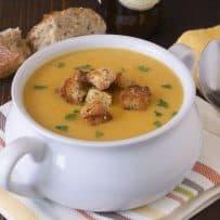 A spoon next to a white soup bowl of soup a la bier (beer soup)