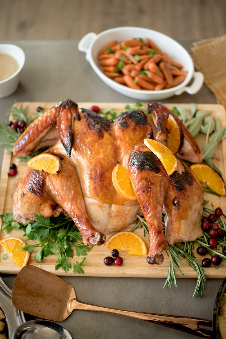 A roasted turkey on a cutting board with oranges and carrots