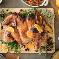 Roasted turkey on a cutting board garnished with fresh orange slices surrounded by herbs