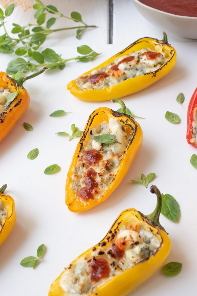 A yellow mini sweet pepper stuffed with blue cheese and topped with hot sauce