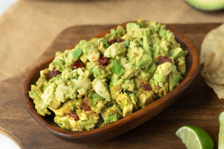 Guacamole made chunky with flecks of chipotle peppers
