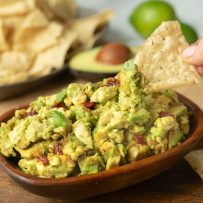 Scooping up guacamole with a tortilla chip