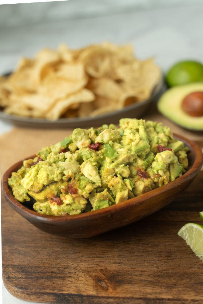 Chunky spicy guacamole in a wooden bowl with tortilla chips
