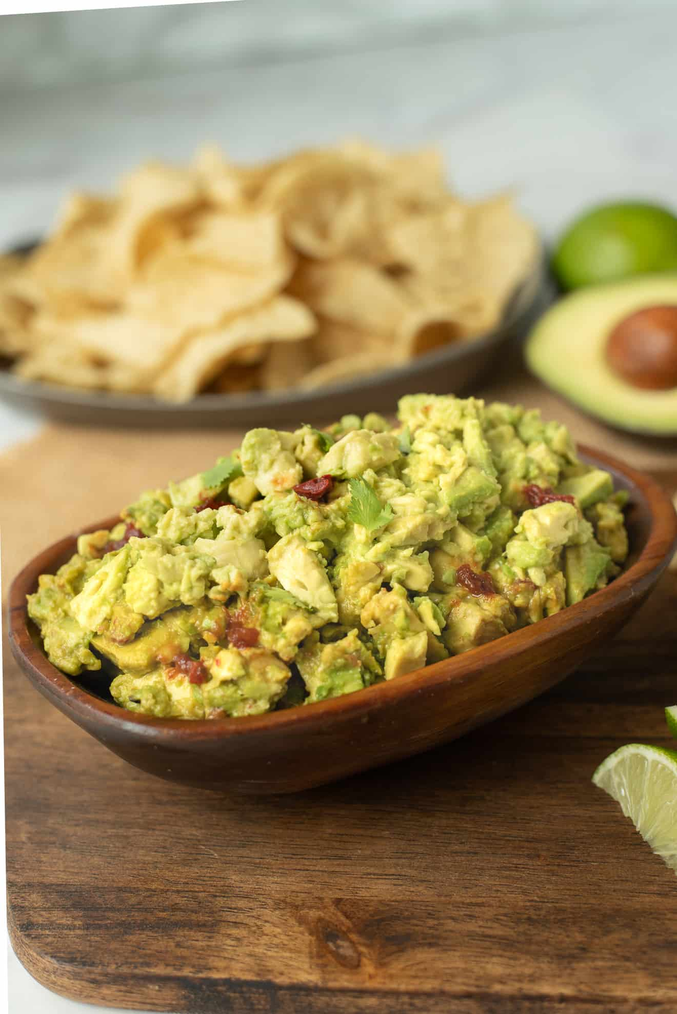 Chunky, spicy guacamole in an oval bowl with tortilla chips