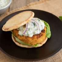 A deliciously browned veggie burger on a naan bun with lettuce topped with raita