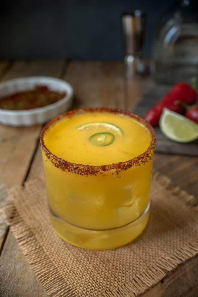 A short glass of Spicy Jalapeño Mango Margarita on a mat