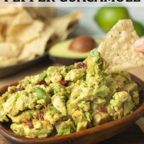 Spicy chipotle pepper guacamole in a wooden bowl