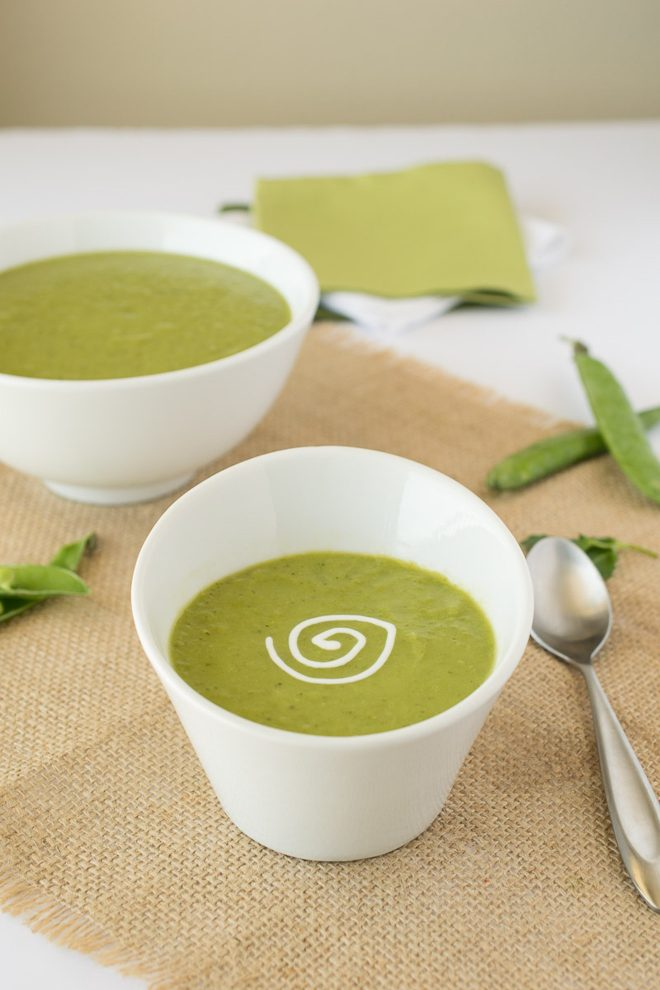 An angled white bowl of pea soup with a sour cream swirl