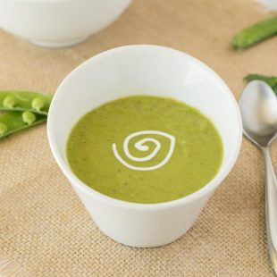 Vibrant green pea soup in a white garnished with sour cream with a spoon and fresh pea pods