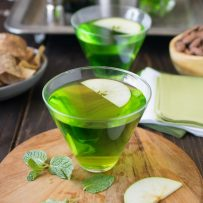 A vibrant green cocktail garnished with sliced apple