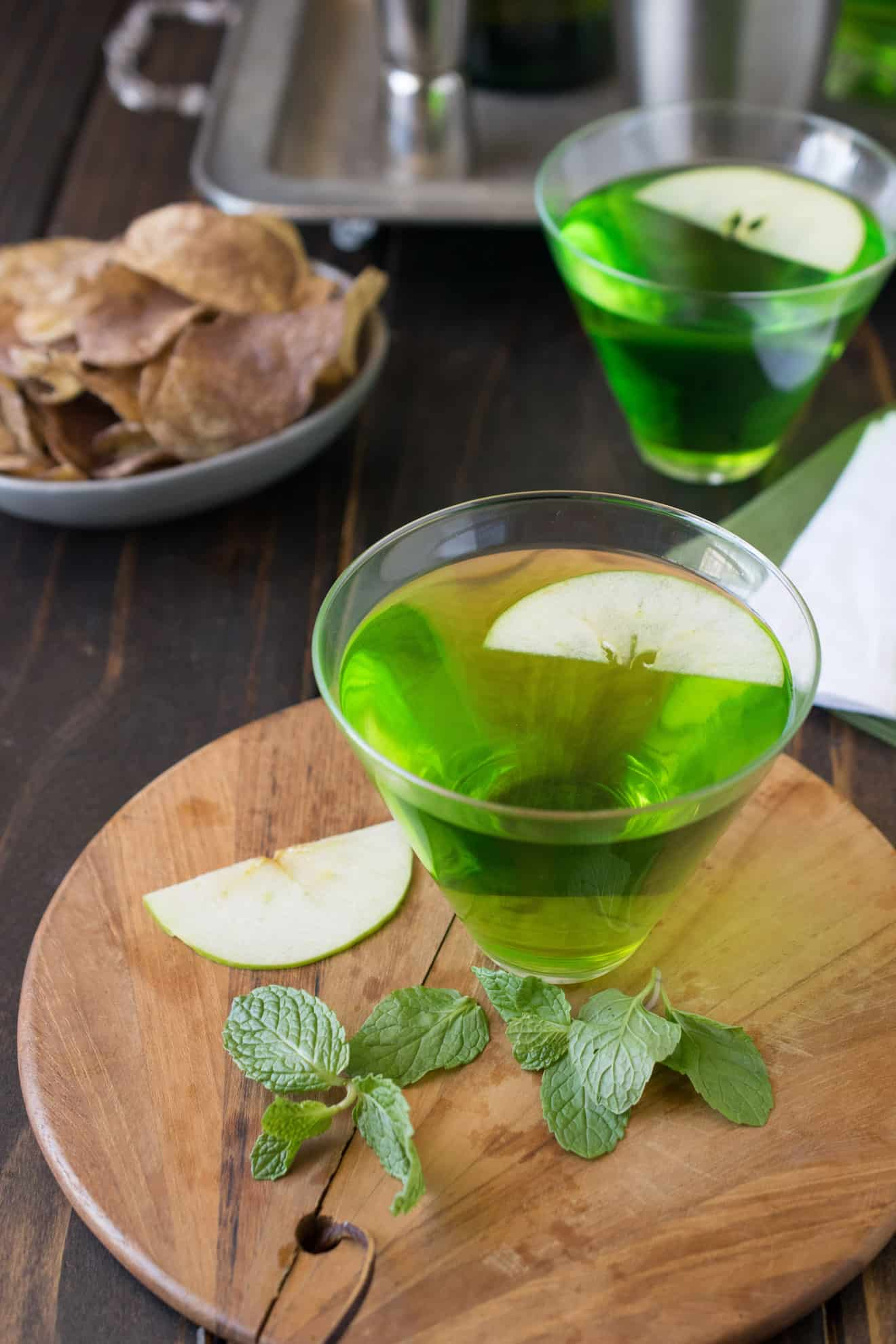2 glasses of St Patrck's Day green Dublin cocktail on a board with fresh mint and apple slices