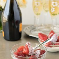 A side view of a glass bowl of whole strawberries with fresh cream with a spoon