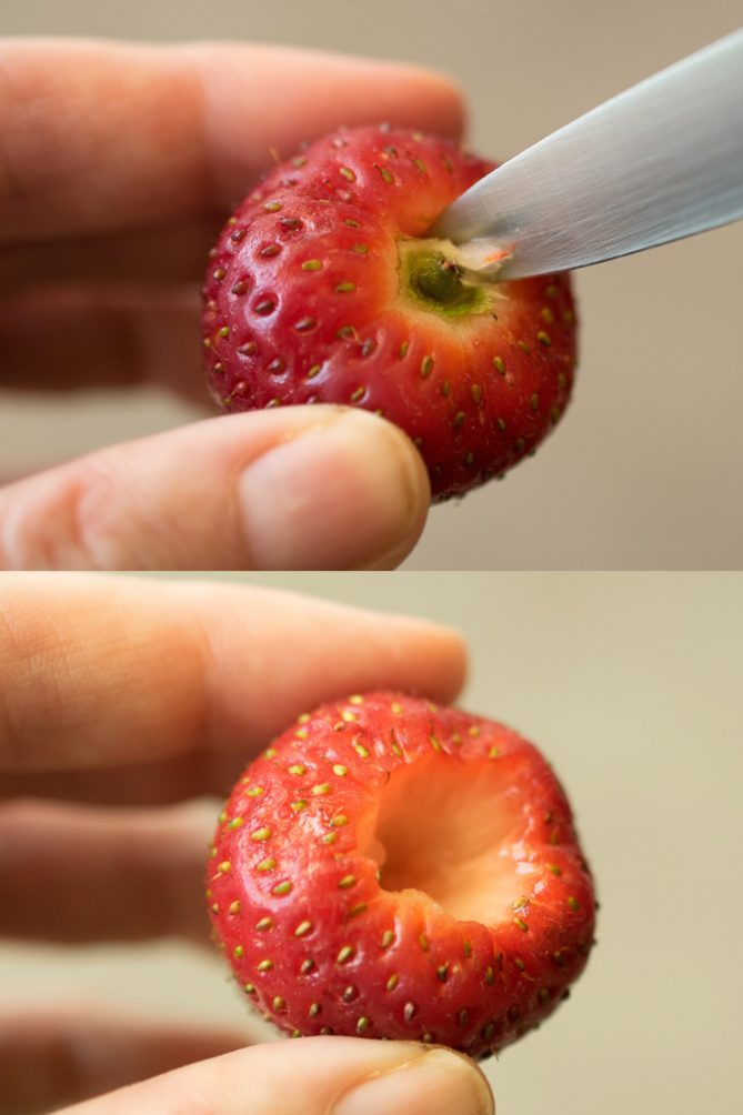 A closeup showing a knife cutting out the hull/stem of a strawberry