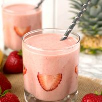 Sliced strawberries decorate the inside of a glass filled with strawberry almond protein power smoothie