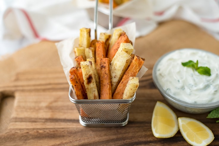 Orange and white baked fries in a basket with yogurt sauce and lemons