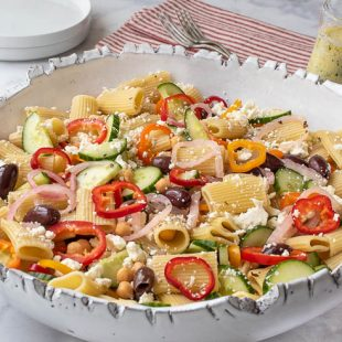 A large white bowl filled with pasta, colorful vegetables, oilves and cheese
