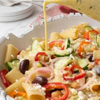 The yummiest and creamy dressing being drizzled over a summer Greek pasta salad