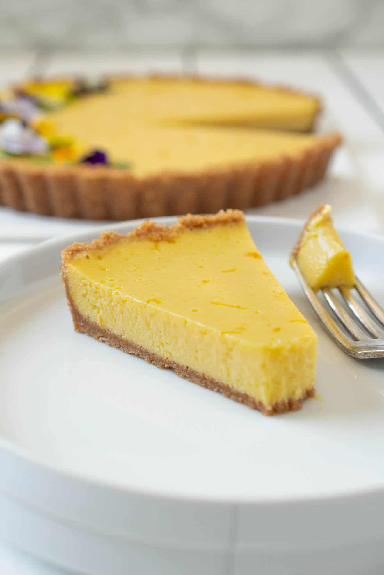 A slice of mango pie on a white plate with some on a fork