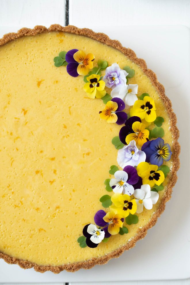 Pretty edible flowers garnish one side of the pie