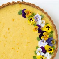 Summer mango pie with half of the top decorated with viola edible flowers