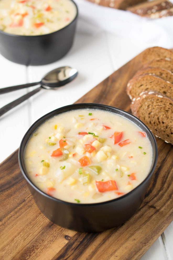 Summer corn chowder served in a black bowl with bread