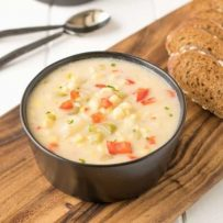 A black bowl filled with corn chowder and red peppers on a board with sliced bread
