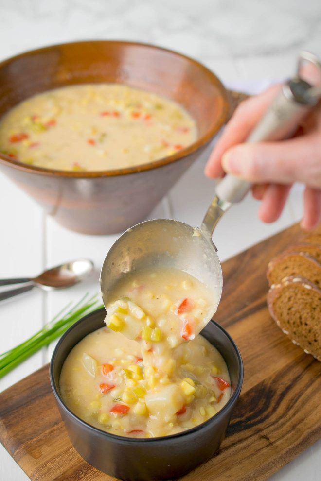 Using a ladle to spoon Summer Corn Chowder into a bowl