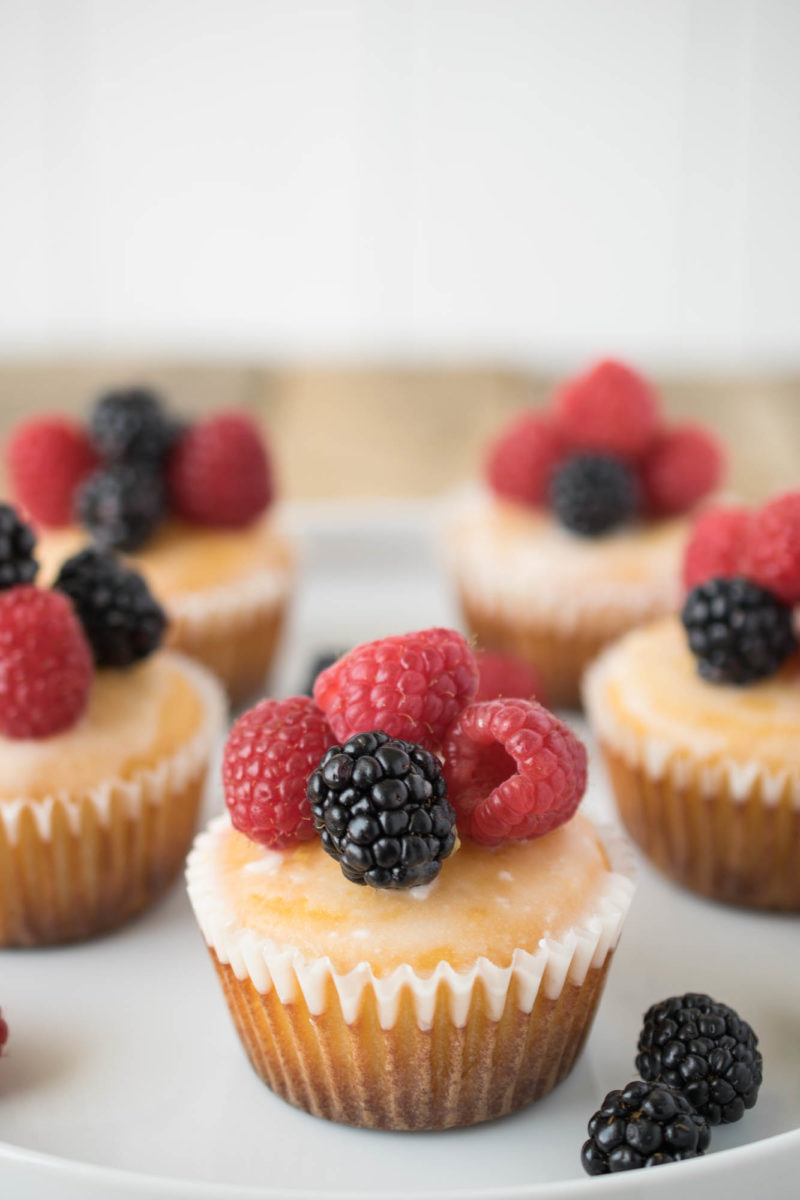 A closeup showing the fresh raspberries and blackberries on top of a muffin