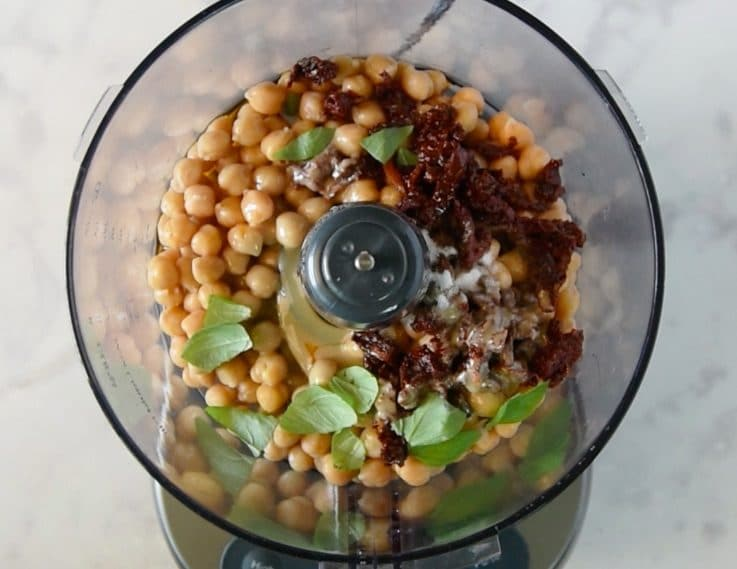 A food processor with chickpeas, sundried tomatoes, tahini, salt and pepper ready to blend into hummus