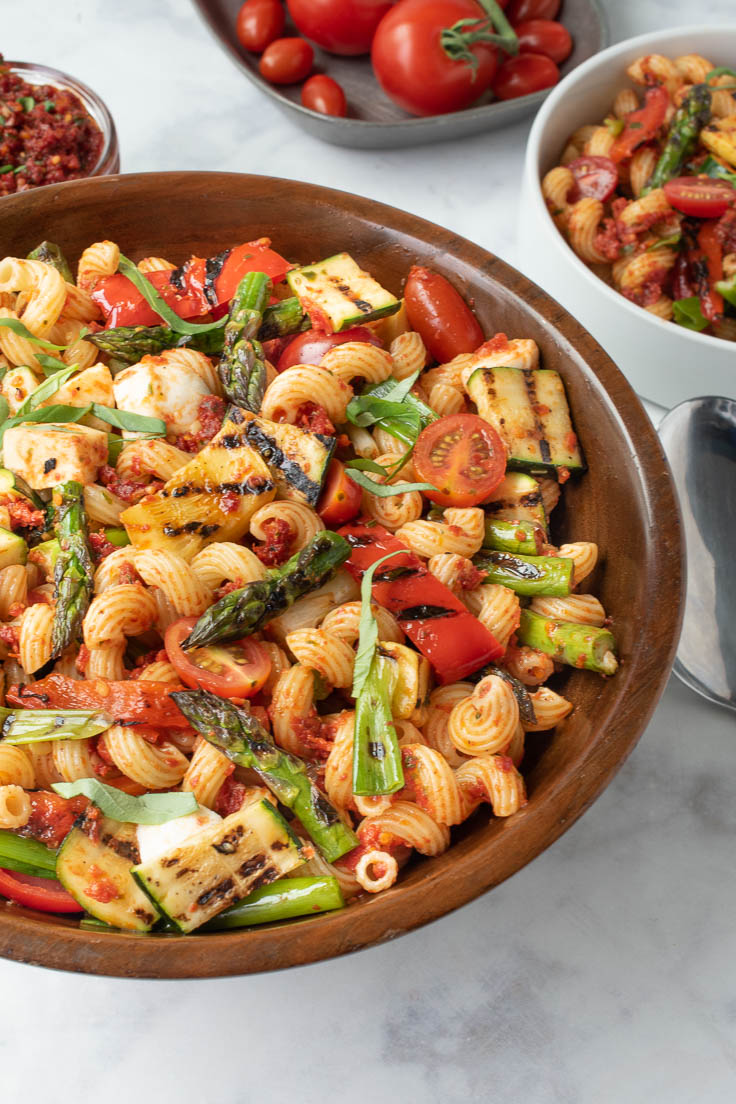 A large bowl of sun dried tomato pesto pasta with grilled vegetables