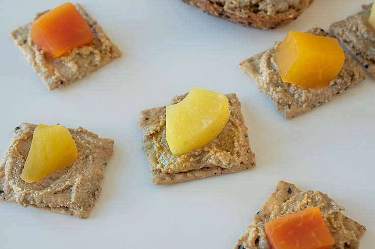 Crackers topped with sunflower butter and tropical fruit