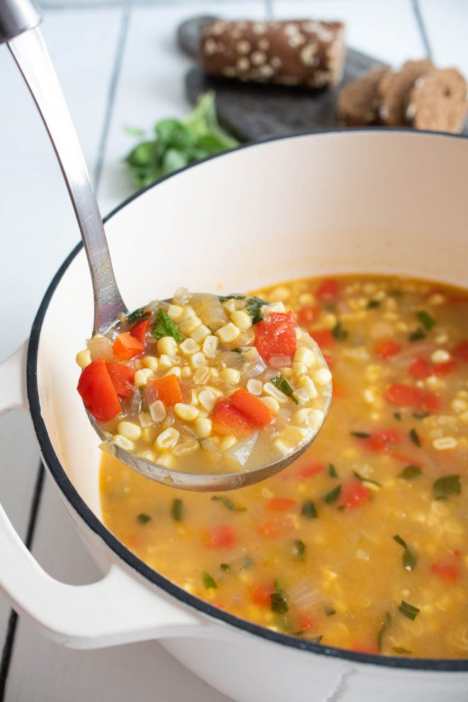 A ladle full of corn and vegetable soup