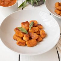 Crispy sweet potato gnocchi served on a white plate with a side of sauce