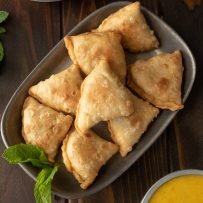 A platter of sweet potato samosas viewed from above with fresh mint