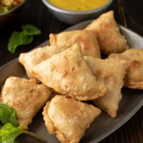 8 sweet potato samosas on a grey plate with fresh mint
