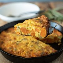 A slice of sweet potato and sage frittata showing the orange sweet potato inside