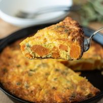 Serving a slice of sweet potato and sage frittata with chunks of sweet potato and sage showed inside
